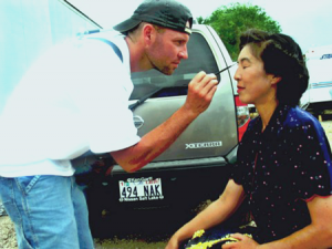 Photo of a man applying makeup to a woman.