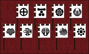 This image shows two rows of banners bearing domain crests. The Satsuma crest is a circle divided into quarters. The Chōshū crest is a horizontal line above three dots. The Ōmura crest is a five-petaled flower blossom. The Okayama crest is a butterfly viewed from the top. The Tsu crest is five, broad, plant leaves. The Yanagawa crest is a cord wrapped around a pair of crossed sticks. The Saga crest is a pair of plant shoots. The Tottori crest is a butterfly viewed from the side. The Kumamoto crest is a large dot surrounded by eight small dots.