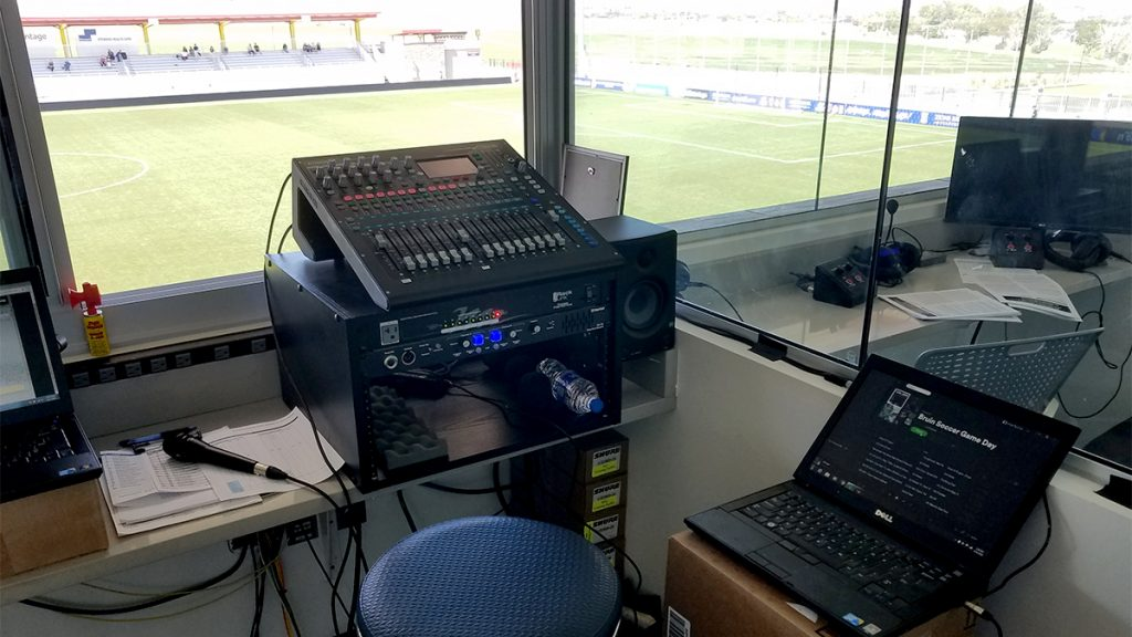 Inside of a soccer broadcast booth sshowing a microphone, sound board, and laptop.